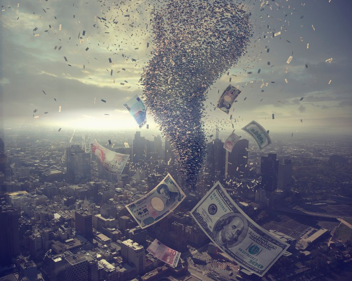 A tornado of paper currency whirls around a city skyline.