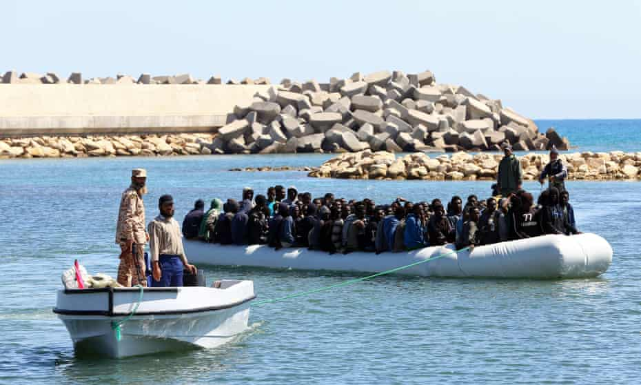 Libyan coastguard officials with people rescued from a dinghy in distress in November 2016.