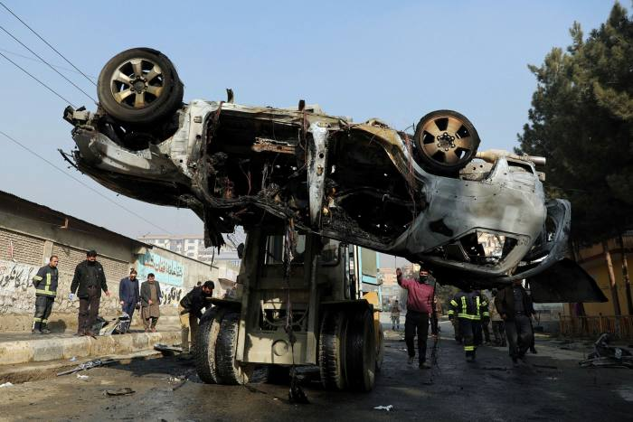 Afghan security personnel remove a damaged vehicle after a deadly roadside bomb attack in Kabul
