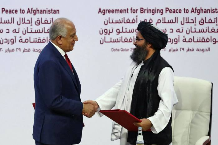 Zalmay Khalilzad, the US special representative to Afghanistan, shakes hands with Taliban co-founder Mullah Abdul Ghani Baradar in Doha last year