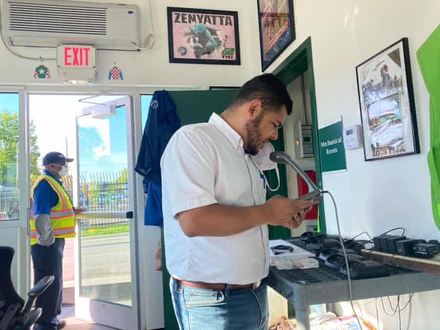 Chaplain Joseph Del Rosario reads a devotional in English and Spanish over the public address system from a security office at Churchill Downs.