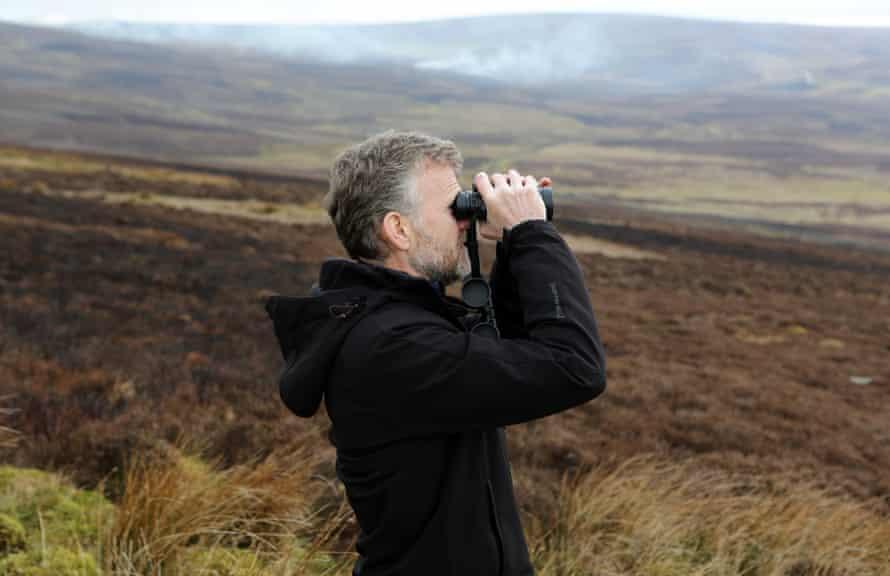 Moorland Monitor Mick Bray looking through binoculars on Barden Moor in the Yorkshire Dales