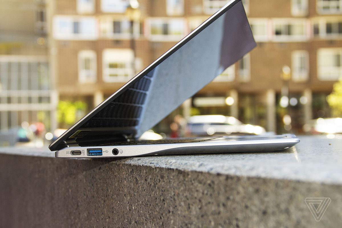 The Acer Chromebook Spin 513 seen from the left, half open, on a stone bench. An apartment building is in the background.