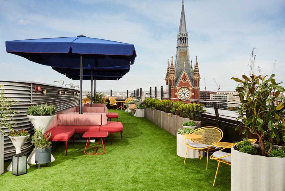 terrace with green grass, blue umbrellas, pink chairs
