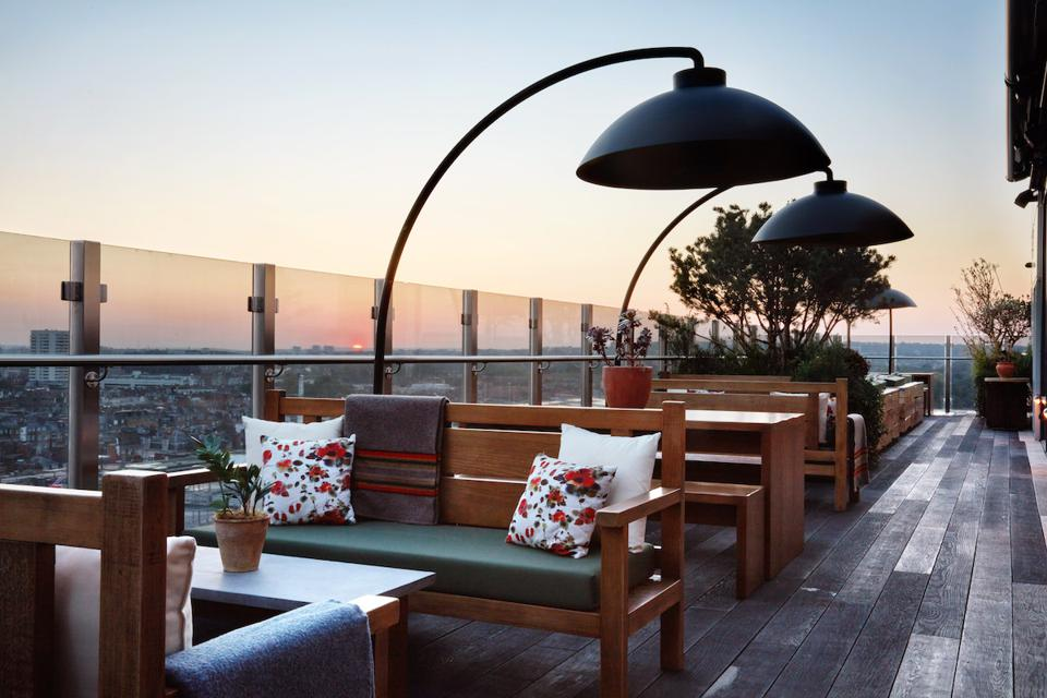 roof terrace with tables, benches and lamps at sunset