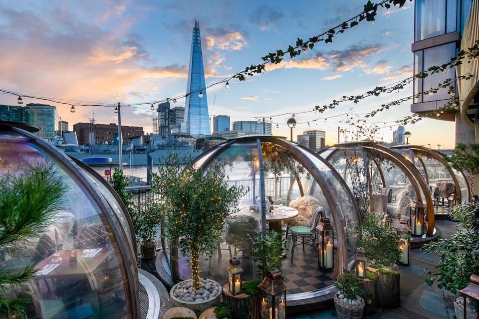 glass igloos with tables and chairs beside river