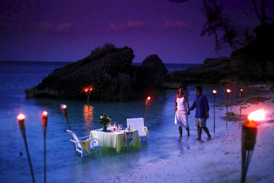 Lovers walk along the water's edge at Cambridge Beaches Resort and Spa, Bermuda.