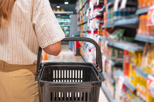 A woman wearing a white shirt and chinos, holding an empty basket in a supermarket.