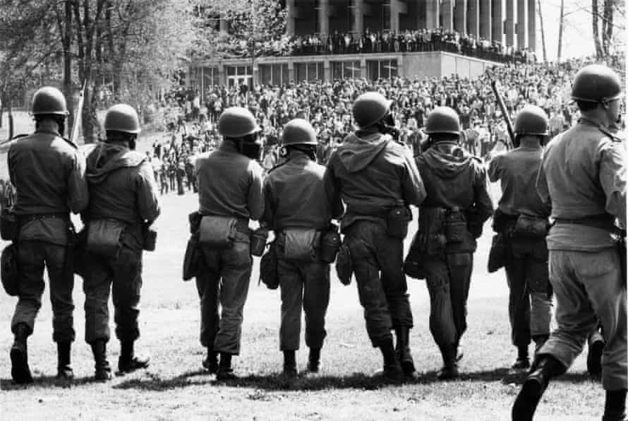 National Guard troops march on anti-war protesters at Kent State University on 4 May 1970; four students were killed.