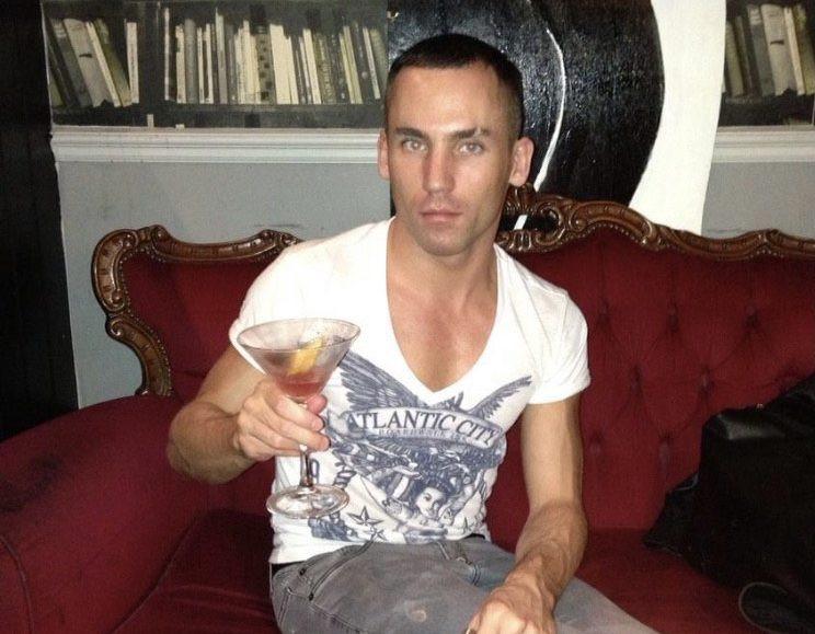 Sam Thomas holding a drink