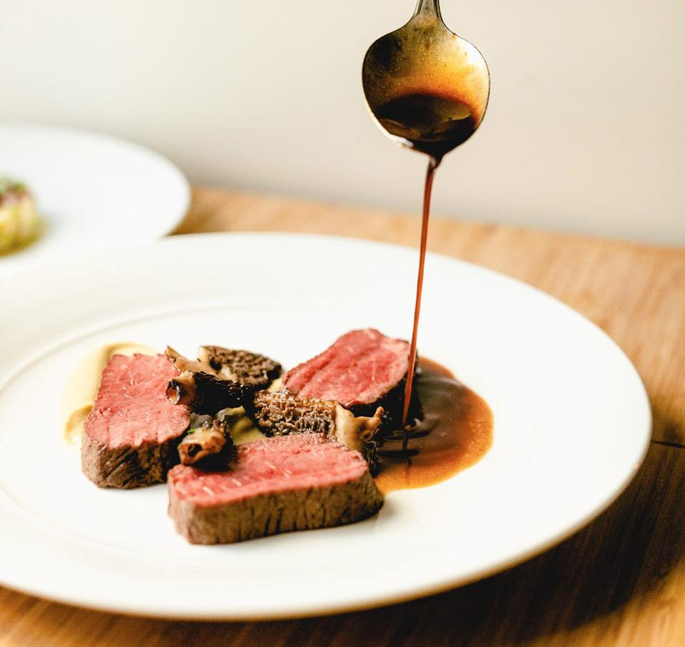 a lamb loin is delicately covered in a jus