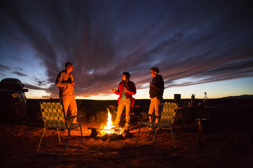 Three friends handing out at a campfire.