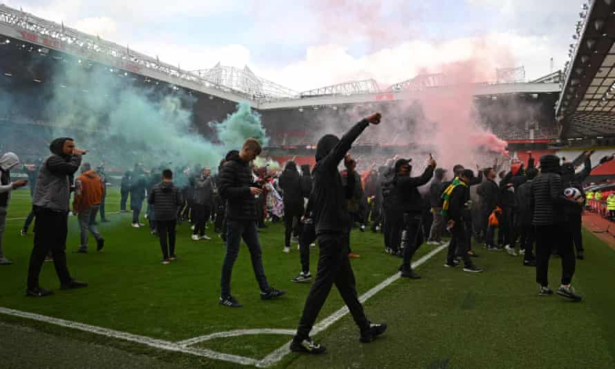 Manchester United supporters on the Old Trafford pitch.