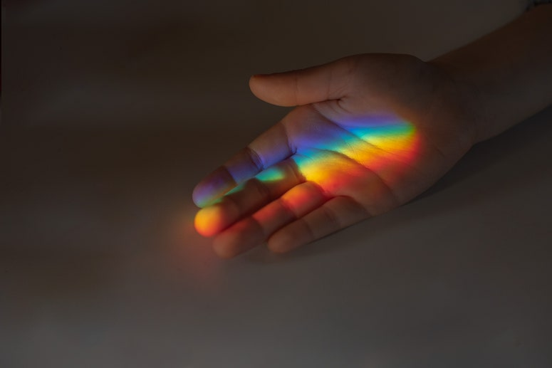 Kid's hand catching a rainbow made with a prism.