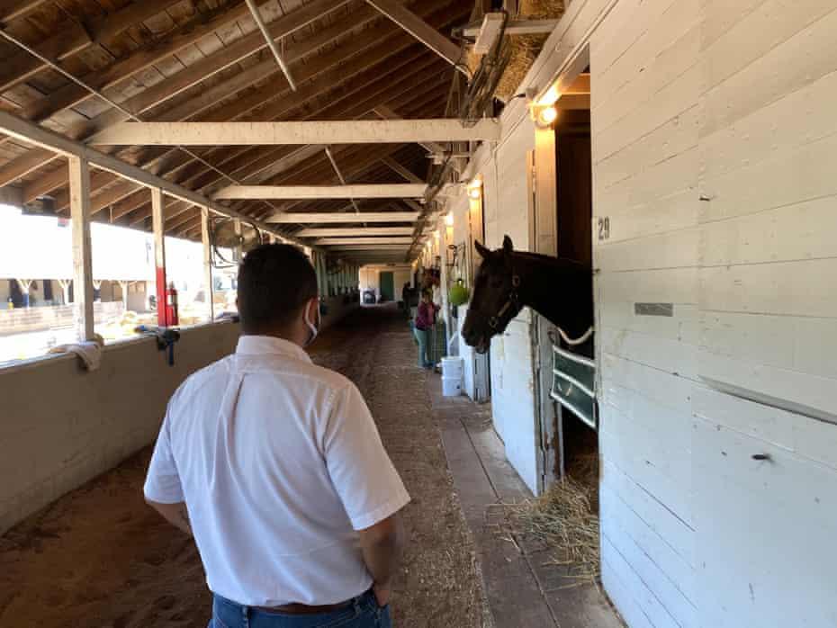 Chaplain Joseph Del Rosario walks in a stable in Churchill Downs.