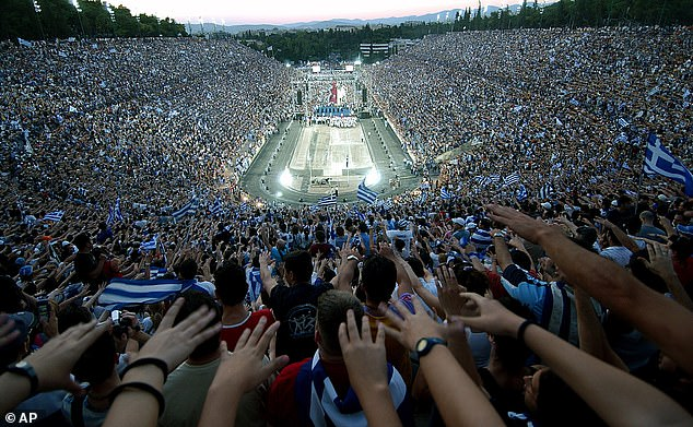 Tens of thousands of fans wave Greek flags and flares at the Panathenian stadium, where the first modern Olympics were held in 1896, to welcome back their Greek heroes from Euro 2004