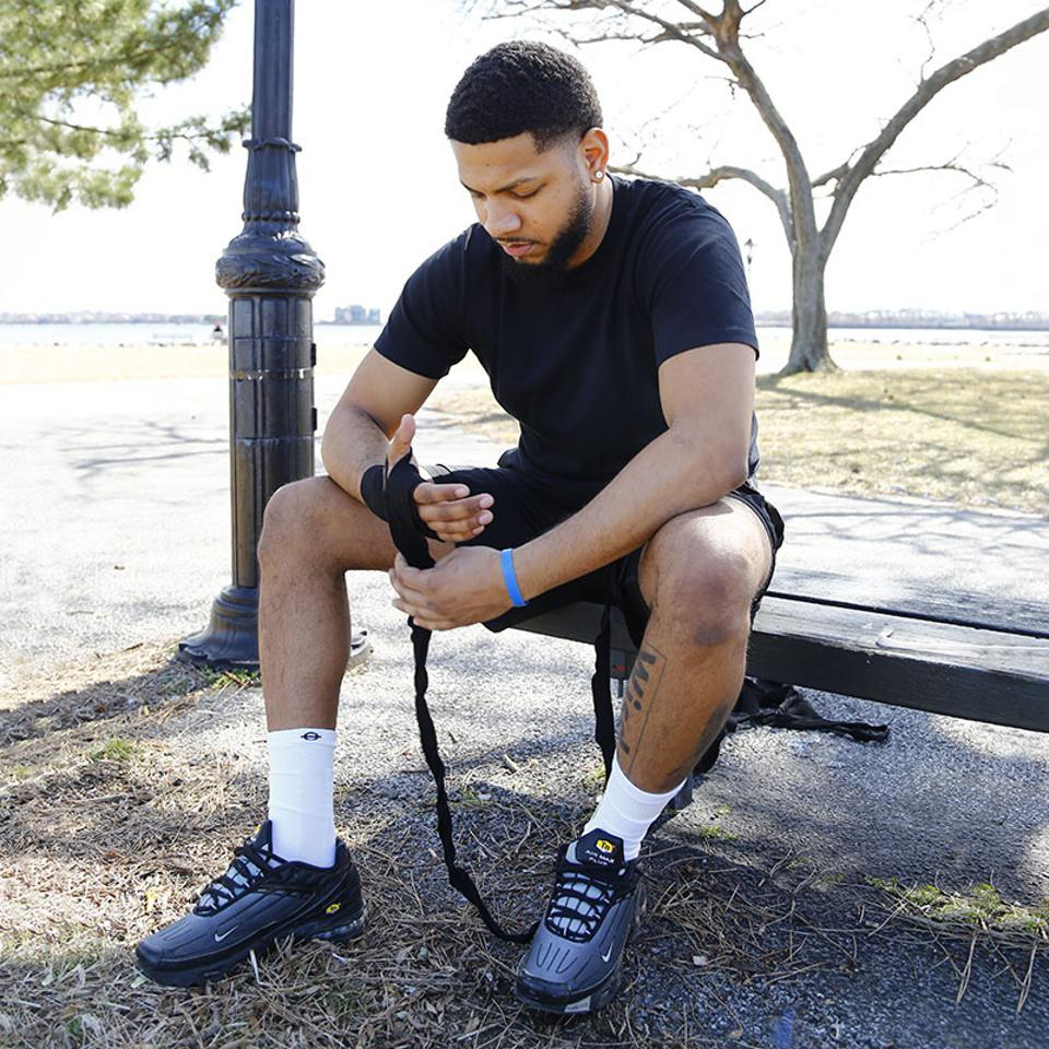 A man wrapping his hands for a workout sits on a bench wearing Lasso compression socks.
