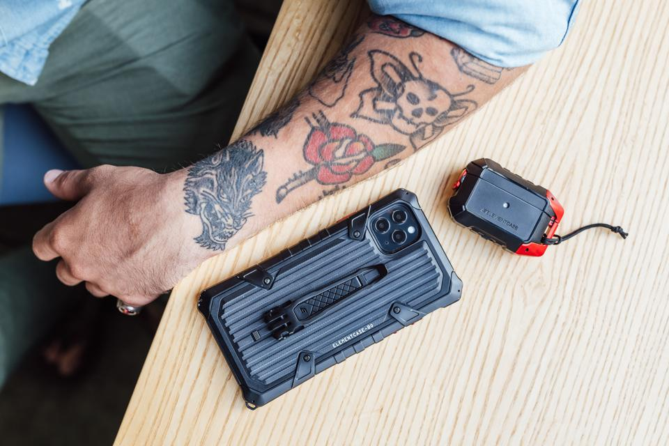 A tattooed man's arm sits next to a phone and AirPods case by Elements Case