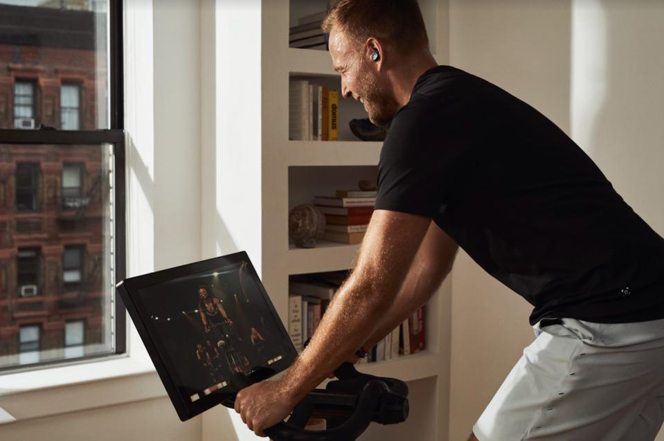 A man in a high-rise apartment cycles on his SoulCycle bike with an instructor on-screen