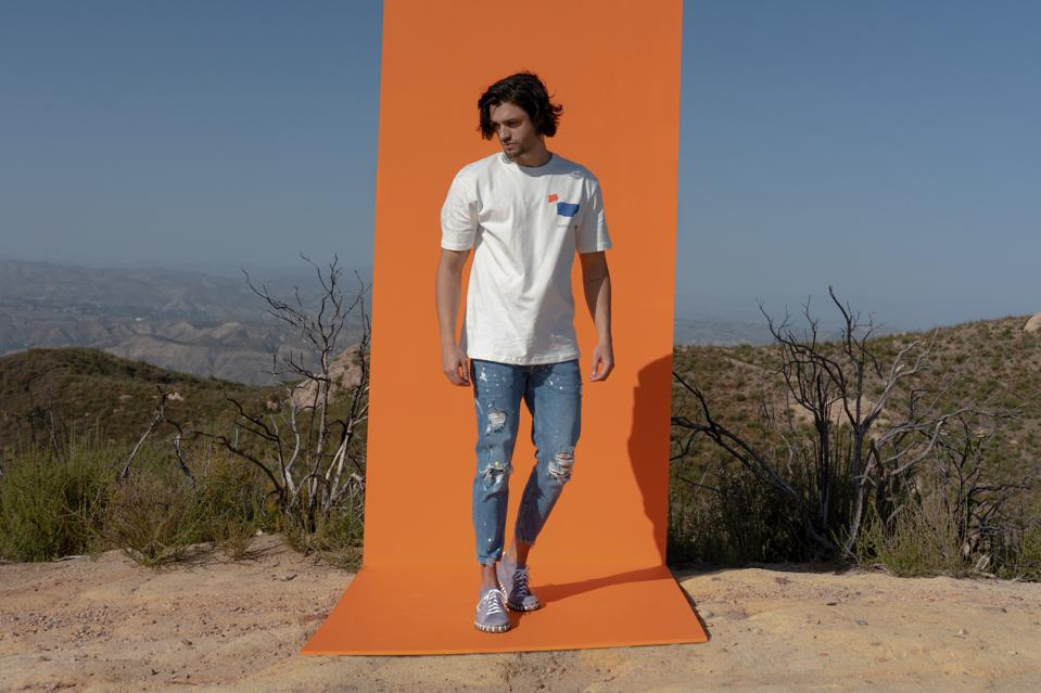 A man with jeans and a tee wears Kengos sneakers in a desert landscape