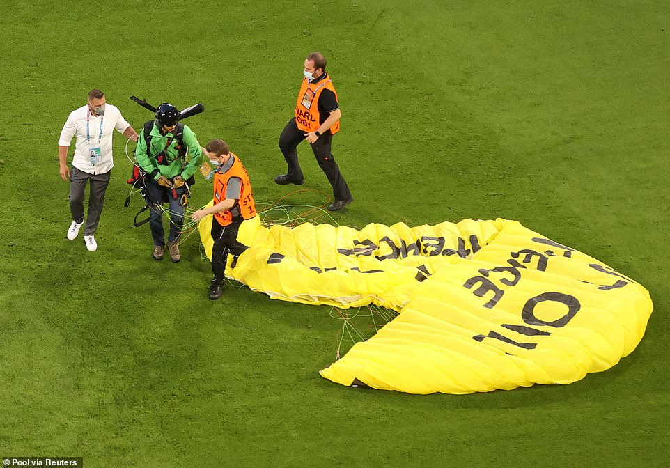 The activist, who had 'Kick Out Oil' emblazoned on his yellow parachute, glided into the stadium before losing control. He was hauled away by stewards after the stunt and later arrested