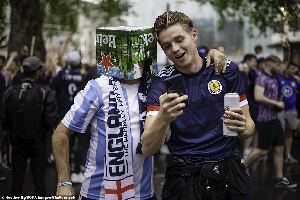 A Scotland supporter speaks with an England supporter wearing a beer box on his head before the Uefa clash
