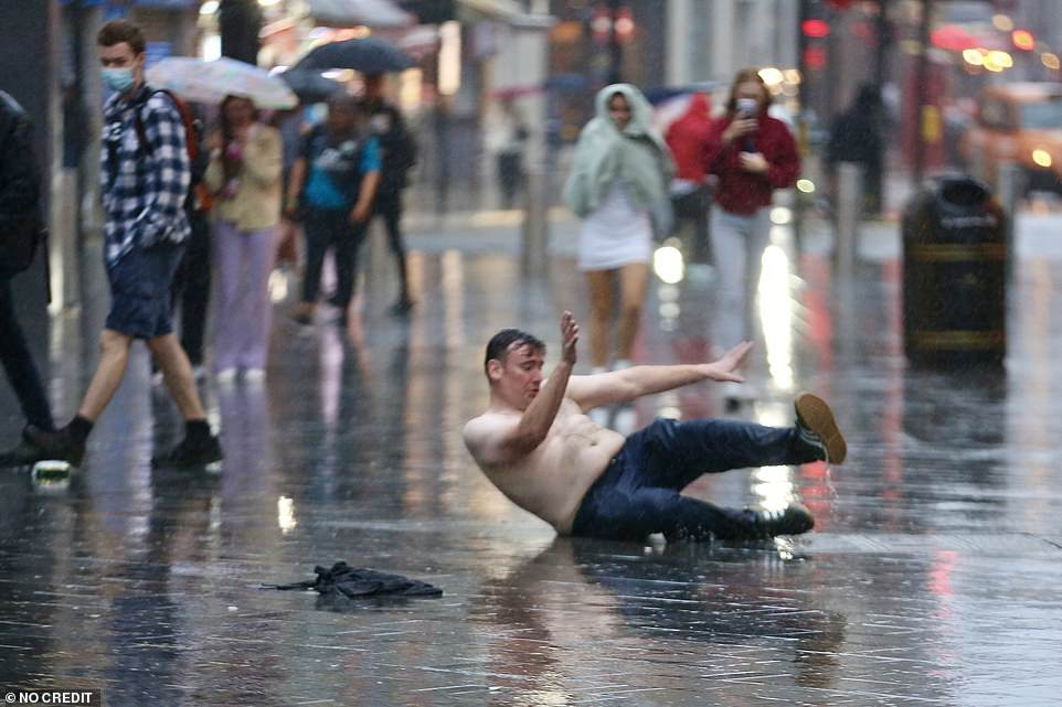 A topless Scotland football supporter falls over in the pouring rain in Leicester Square, central London