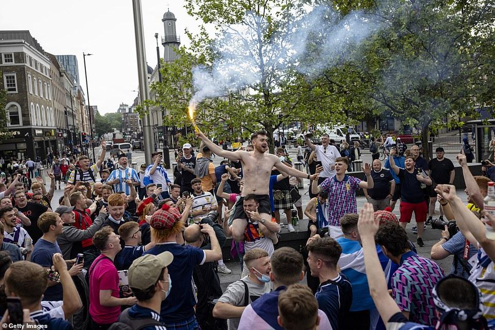 A Scotland fan lets of a flare outside King's Cross Station on June 17, 2021 in London