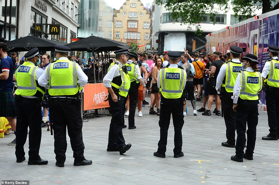 Metropolitan Police officers are seen in Leicester Square as Scotland football fans sing and drink ahead of the Uefa clash