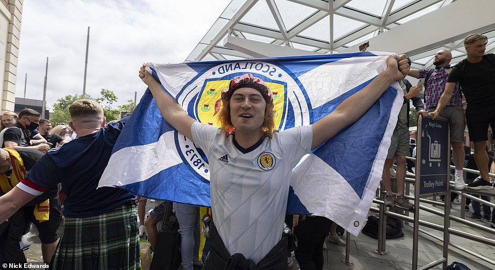 One fan was seen smiling with a hat and Scottish flag as fans gathered at King's Cross Station in the capital