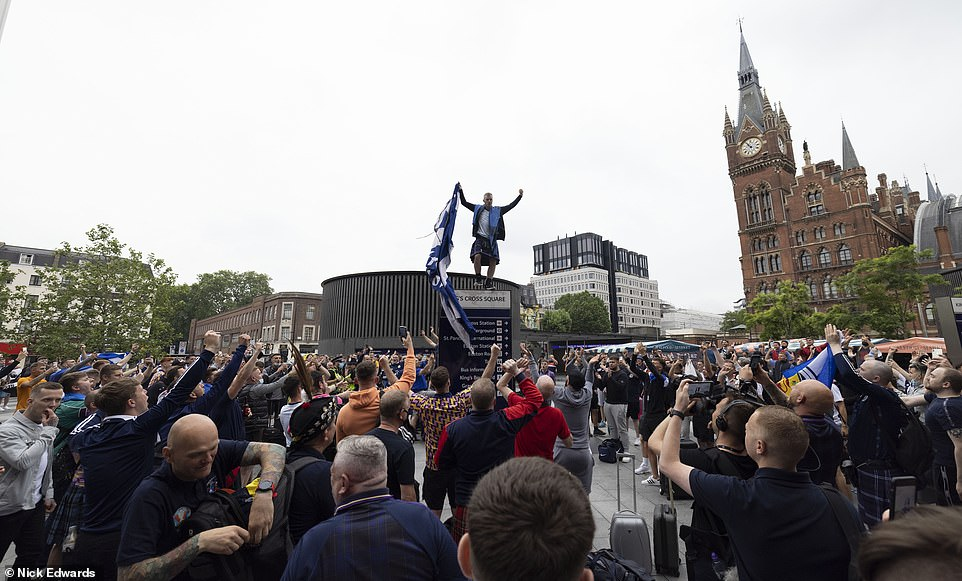 It is thought that Scotland will join England in taking a knee to protest racial inequality during Friday's game. Pictured: Scotland fans at King's Cross Station