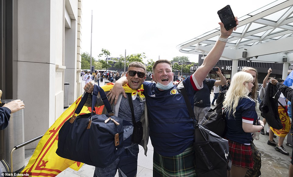 Football fans beam as they pose for a picture ahead of the Scotland vs England match