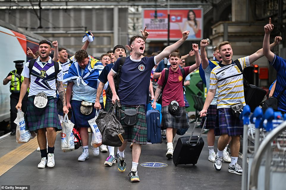 Fans wearing kilts chanted and punched the air as they walked down the platform in Glasgow