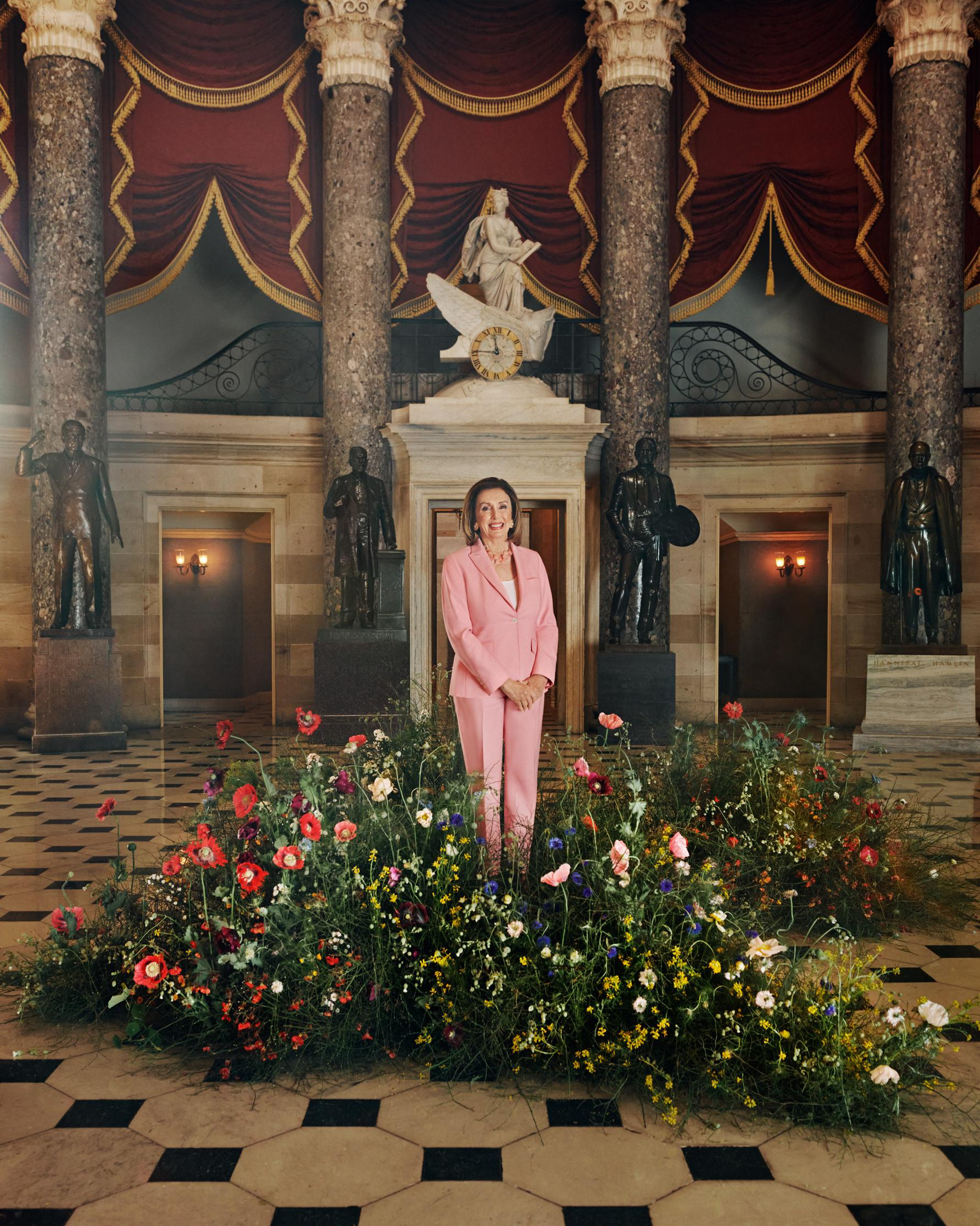 Speaker of the House Nancy Pelosi stands indefatigable amidst a fertile mound of earth and wildflowers installed in the National Statuary Hall in the U.S. Capitol.