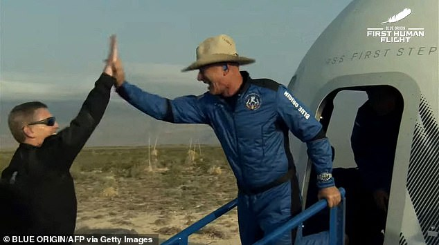 Jeff Bezos (right) celebrates after exiting Blue Origin's reusable New Shepard craft capsule returned from space, safely landing on July 20, 2021