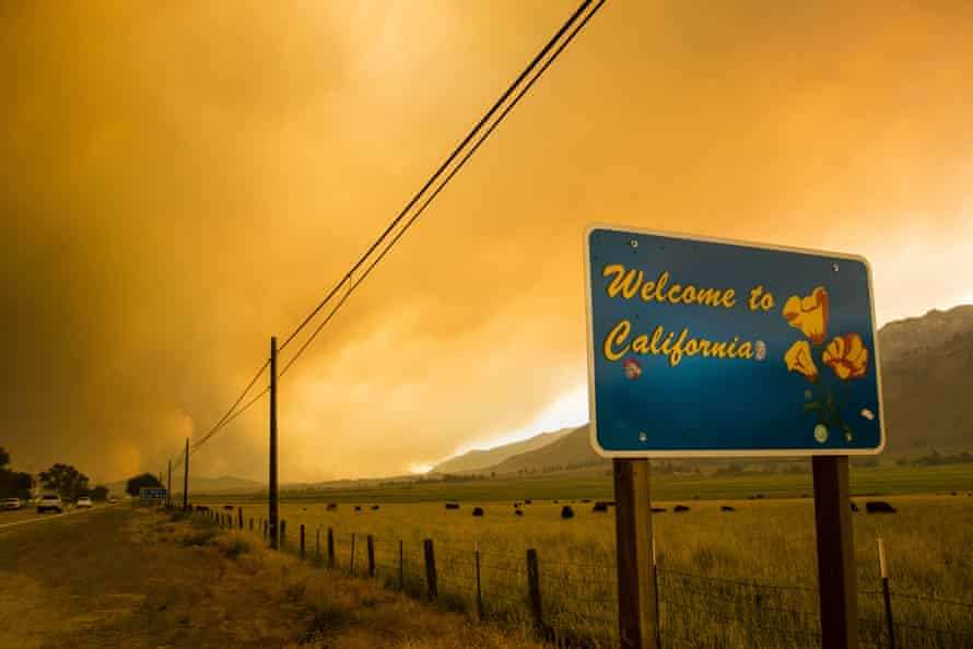 A sign in Markleeville welcomes people to California as smoke from the Tamarack fire rises in the background.
