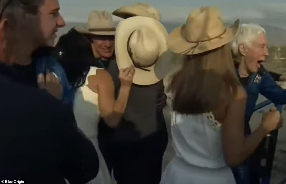 Lauren Sanchez kisses Jeff Bezos on the cheek after he touches down in Van Horn, Texas, after returning from space on New Shepard on Tuesday morning with Wally Funk, far right, Oliver Daemen, far left, and his brother Mark, not shown. Mark's wife is shown approaching Wally in white to celebrate the successful space flight