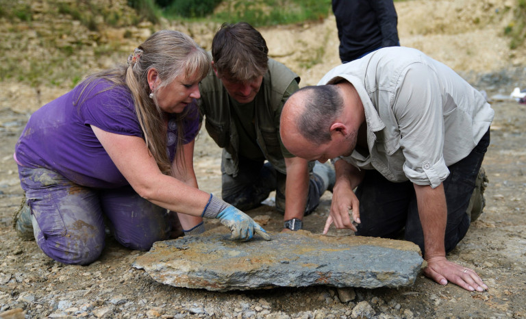 Neville (left) and Sally Hollingworth join Dr Tim Ewin from the Natural History Museum, as they inspect a slab during a dig in a quarry in the north Cotswolds, where preserved echinoderms, sea lilies and echinoids, dating back to middle Jurassic period, have been found after the site was discovered by them.