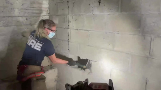 Video grab of Jenny Adkins of the Cincinnati Fire Department rescuing a dog that had been missing for five days ? after it got stuck between 2 walls! See SWNS story SWOCdogrescue. This is the moment a dog that had been missing for five days was rescued from between two walls and reunited with her owner. Missing posters had been up for the best part of a week in Cincinnati, Ohio, USA for Gertie, a small dog who had fallen down the crevice behind a garage. Her two owners, Connie Frick and Lynn Herman, were overcome with emotion when their pooch bounded over after being rescued by the fire department who cut a hole out the concrete wall. Resident Vanessa Roland heard a dog crying behind her neighbour's garage wall and alerted them to the noise last Sunday (18/07).