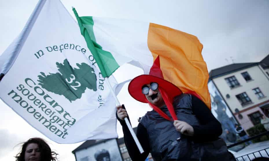 A protester with republican and Irish flags at a demonstration marking the funeral of Margaret Thatcher in Derry, April 2013