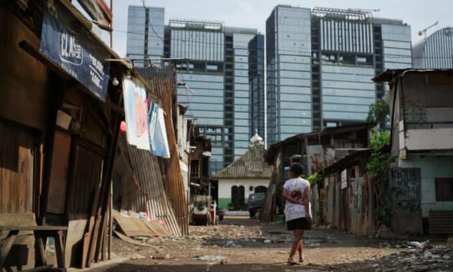 A woman walks in the slum area of Jakarta
