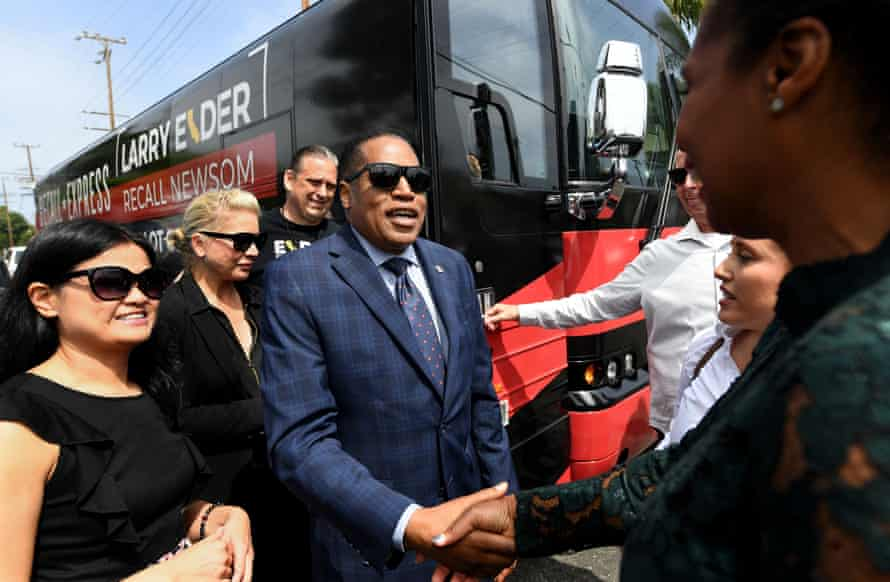 Elder shakes hands with people near campaign bus