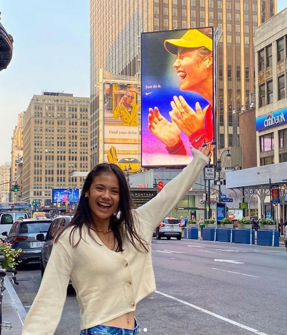 Global fame: Raducanu poses with her photograph on a billboard in New York's Times Square