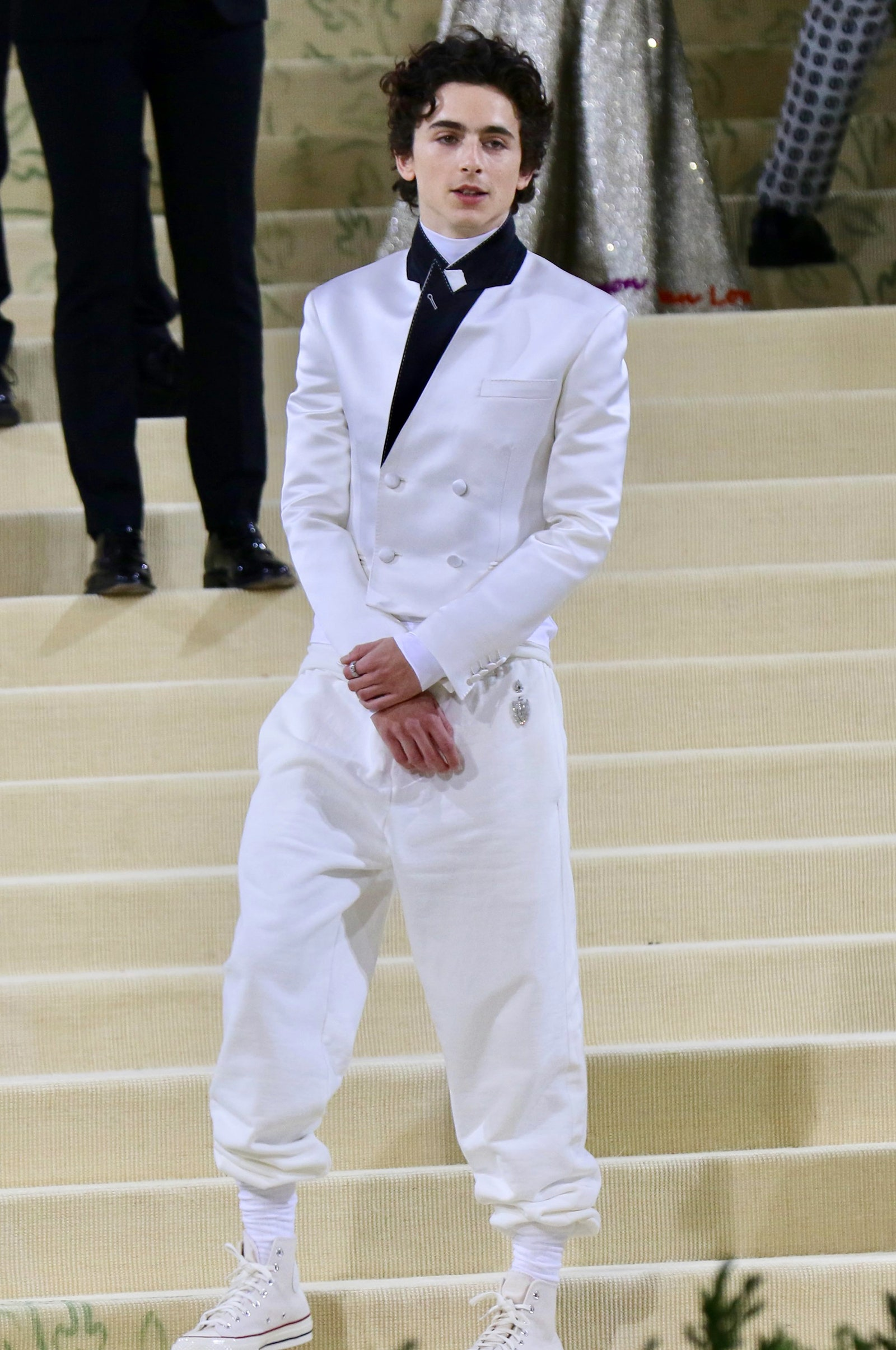 Timothee Chalamet wearing a white suit and black shirt at the MET gala.