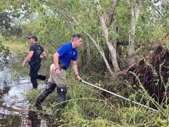 Sgt. Devin Coulon and Cpl. Chance Woods of the St. Tammany Parish Sheriff's Office searching for an alligator believed to have killed a man after Hurricane Ida in Slidell, Louisiana.