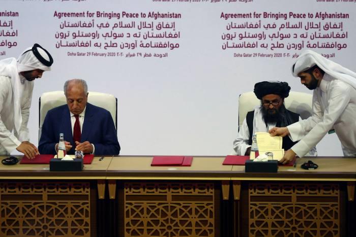 Abdul Ghani Baradar, right, leader of the Taliban delegation, signs an agreement with Zalmay Khalilzad in Doha, Qatar, on February 29 2020