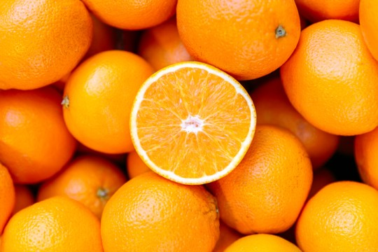 Half of orange on the heap of oranges