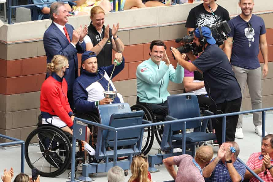 Dylan Alcott pours a beer next to Diede de Groot