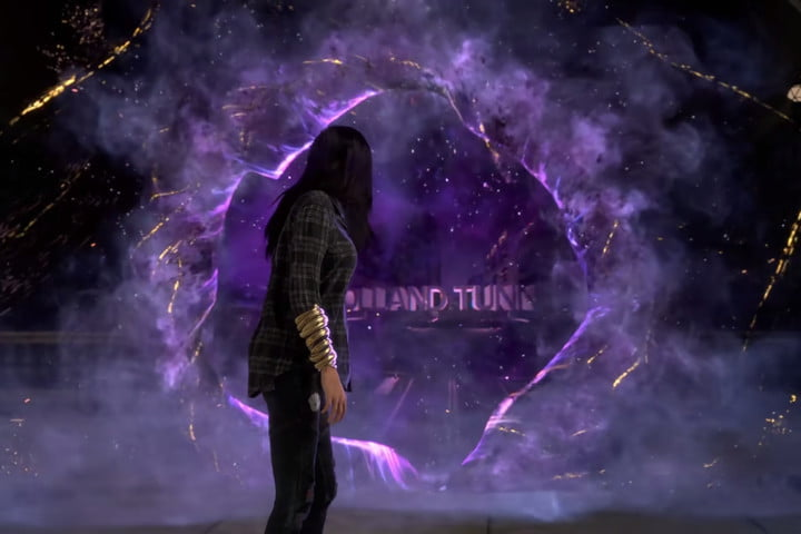 The protagonist of Forspoken looks through a purple portal.