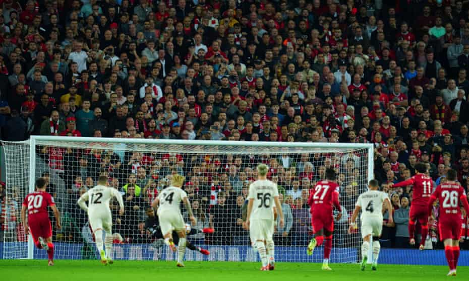 The home fans watch in disbelief as Mike Maignan saves Mohamed Salah's penalty.